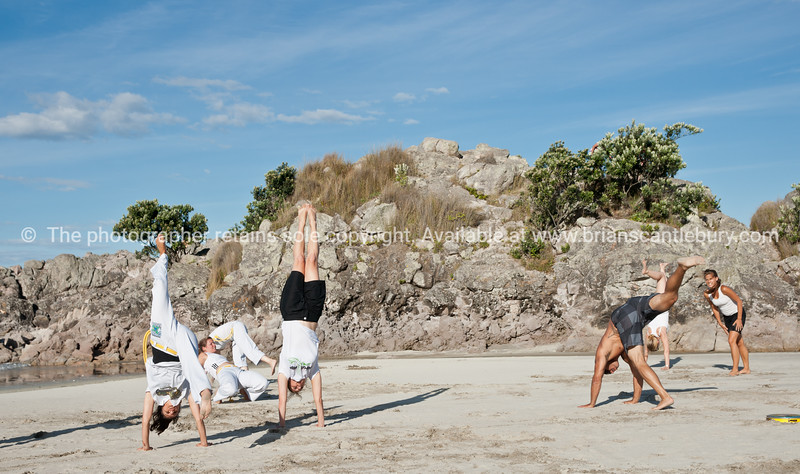 """Capoeira being practised on Mount Maunganui beach, Tauranga, New Zealand.<br /> Capoeira is a game, a sport, an art and a life philosophy, founded in Brasil in 1984.-2<br /> Model Release; no. See;  <a href=""""http://www.blurb.com/b/3811392-tauranga"""">http://www.blurb.com/b/3811392-tauranga</a> mount maunganui landscape photography, Tauranga Photos; Tauranga photos, Photos of Tauranga Also see; <a href=""""http://www.brianscantlebury.com/Events"""">http://www.brianscantlebury.com/Events</a>"""