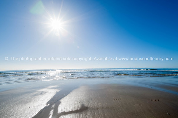Papamoa Beach. Sun in sky over the horizon and beach.
