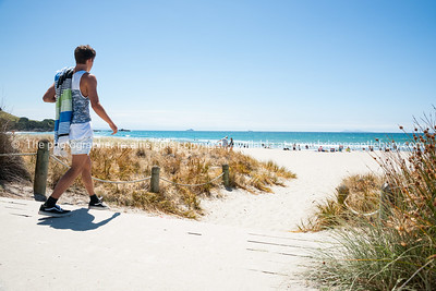Young man, towel over shoulder, walks to the beach. Mount Maunganui beach scenes.