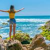 Girl in yellow top on coastal rocky seaside.