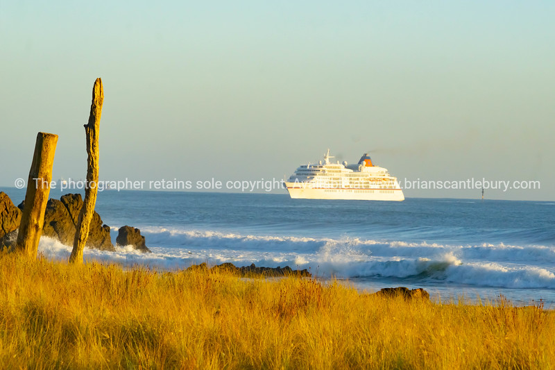 Small cruise ship approached Tauranga harbor entrance at base of Mount Maunganui
