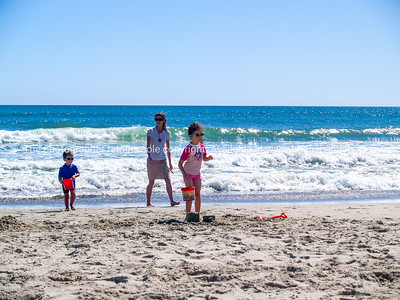 Mum and two small children build sand castles.