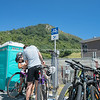 Cyclists carrying out running repairs at public bike repair station with landmak mountain background