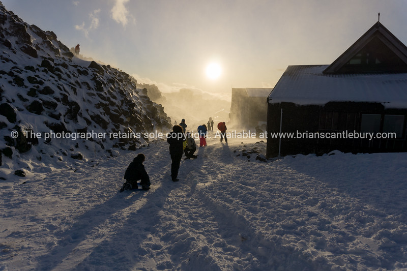 People caughtin sudden gust of wind and windblown snow silhouetted by setting sun