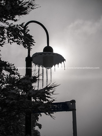 Iclcles hang from silhouetted street lamp.