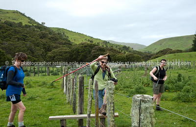 Three women cross a stile on Tora Walk. New Zealand Image.