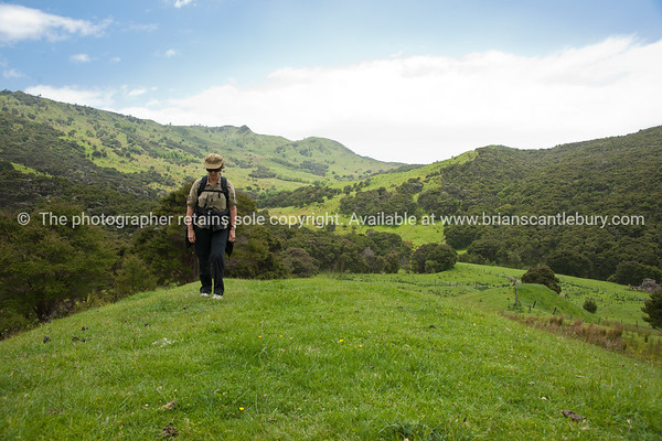 Woman tramping cross country. New Zealand Image.