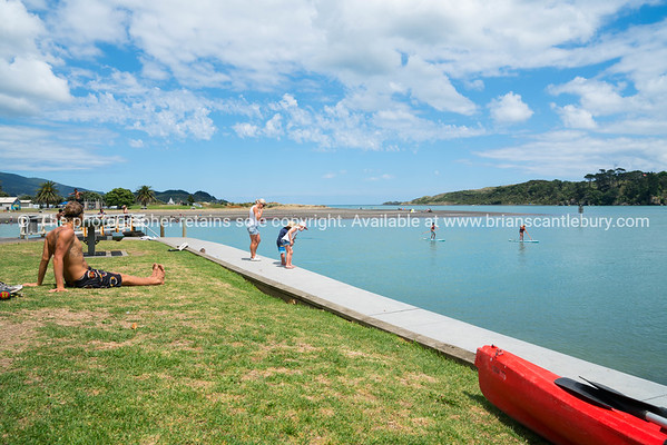 Summer fun in Raglan children fishing with mother on harbour edge while man sits in sun.