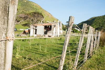 Old tumbled down corrugated farm shed beyond rickety fence in hilly land.