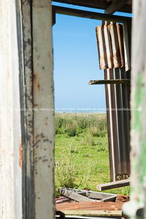 Wairarapa Coast at Tora beach through remains of dilapisdated shed opening