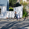 Woman walks through shadow of leafless tree past electric hire scooter on pavement and a weatherboard home.