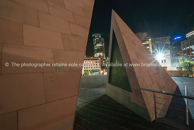 Te Aho a Māui split pyramid sculpture with path through leading to Civic Square and city lights and scenes Wellington New Zealand