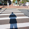 Long shadow in afternoon sun, person waits at pedestrian crossing