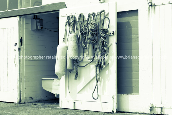 Hanks of rope hanging on inside boats sheds on harbour edge with open door  and dinghy stern in opening.
