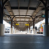 Train station platform long interior shadows with people moving through.