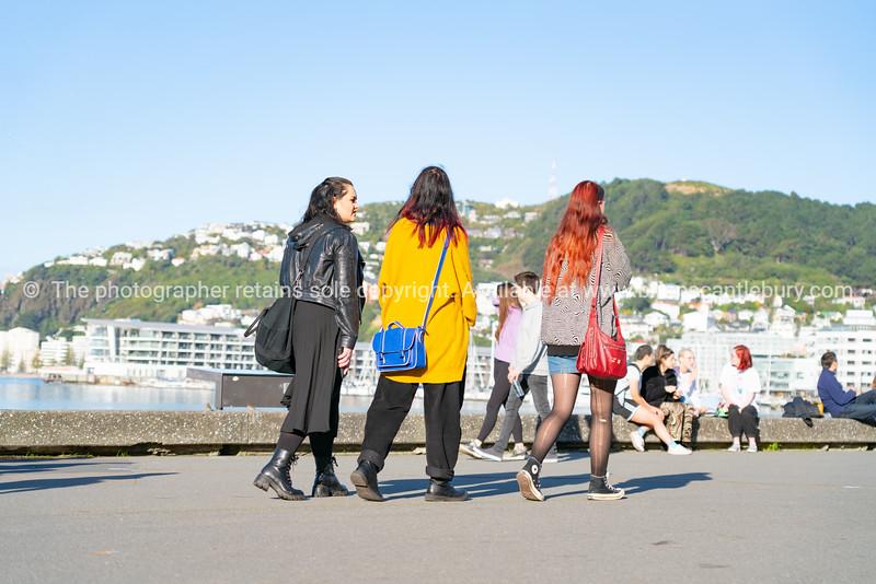 Three women   walking away along along Great harbour Walk on city's water edge.