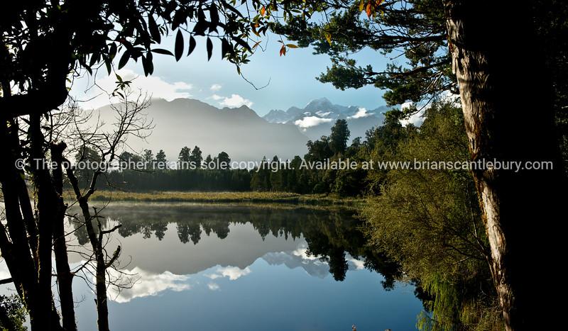 Lake Mathieson, Westland, New Zealand. Beautiful reflections, framed by native bush. New Zealand photographic stock images. South Island