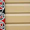 Traditional Maori design and colours as vertical frieze on building exterior. New Zealand photographic stock images.