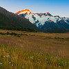 Sun at sunrise strikes snow-capped mountian peaks beyond silhouette of foreground hills of Southern Alps, Canterbury New Zealand.