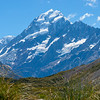 sunshine strikes snow-capperd Mount Cook byond valley below