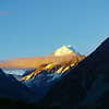 Snow capped mountain catches last of evening sun framed by silhouette of slopes