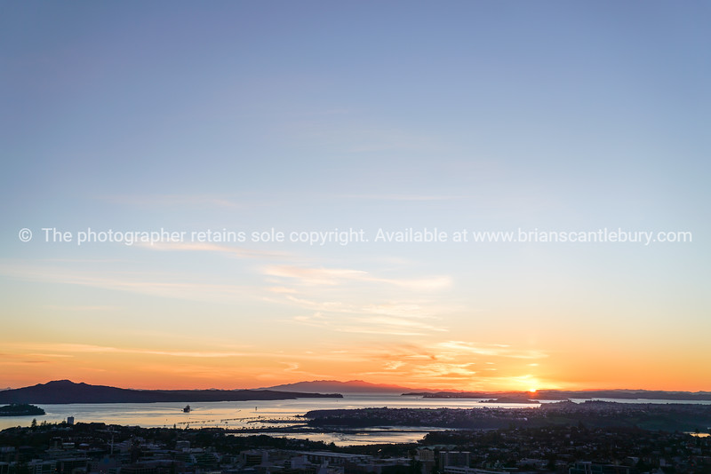 Auckland city and Rangitoto Island in silhouette at sunrise from top Mount Eden, New Zealand.