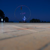 Circular modern coastal sculpture with bird on path along beach in selective focus at night agaignts dark sky.