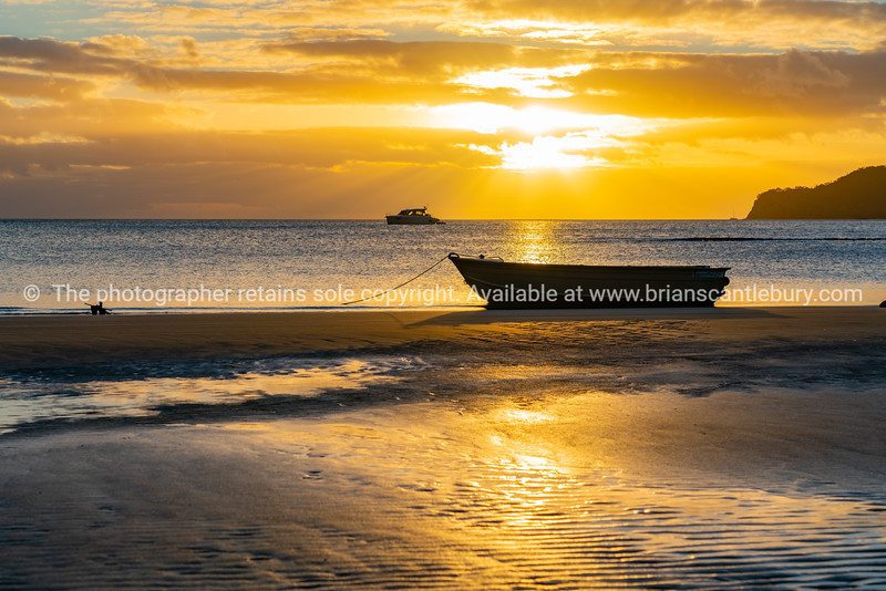 Setting sun glistens on water and sand patterns with dinghy silhouette on beach at low tide