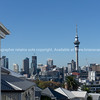City central business district and landmark Skytower in distance viewed from Ponsonby across roof tops of villa homes in foreground.