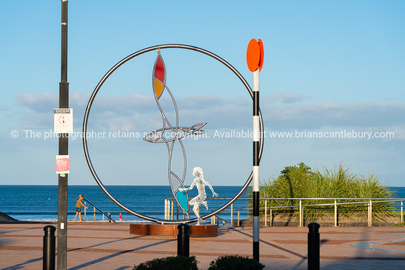 Circular coastal sculpture with bird on path along beach