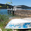 Old dinghy upturned at wharf and harbour at Okupu Bay