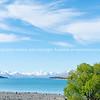 White clouds drit through blue sky above Lake Tekapo