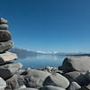 Stone stacks on shore of Lake Pukaki with Southern Alps in distance across lake.
