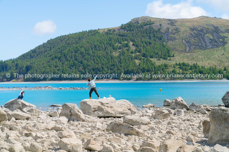 Two young tourists  enjoy experience of rocky foreshore taking photo