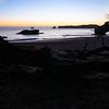 Golden glow on horizon beyond silhouette beach foreground