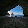 Te Hoho Rock standing in sun framed by the natural arch of Cathedral Cove on Coromandel Peninsula New Zealand.