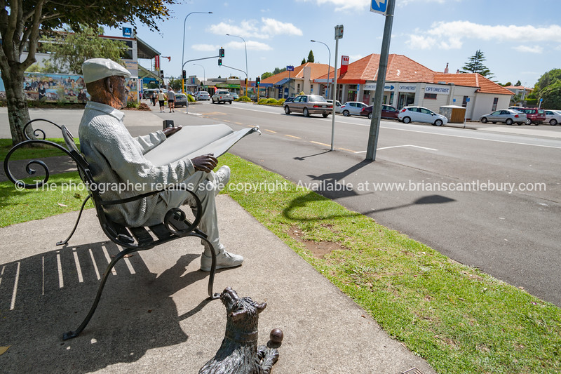 Bronze statue of man sitting on park bench reading newspaper in Katikati.