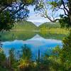 View through framed trees across Blue Lake