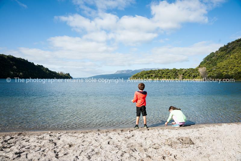 lake tarawera, two children playing at waters edge.