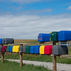 Rows if multi-coloured rural lexxterboxes on country road