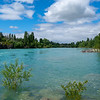 Beautiful turquoise water of Clutha River flowing between diminishing perspective of willow covered river banks.