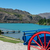 Red and blue cart at top of path leading to jetty into turquoise river surrounded by Central Otago hills at Cromwell historic precinct