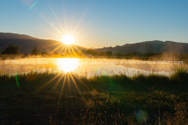Mist rises over pond as sunrises and warms the air in rural Cromwell