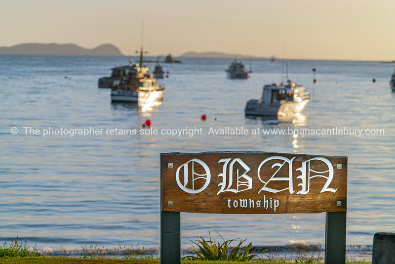 Wooden sign with towhship name of Oban at waters edge to bay