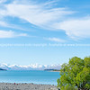 White clouds drit through blue sky above Lake Tekapo