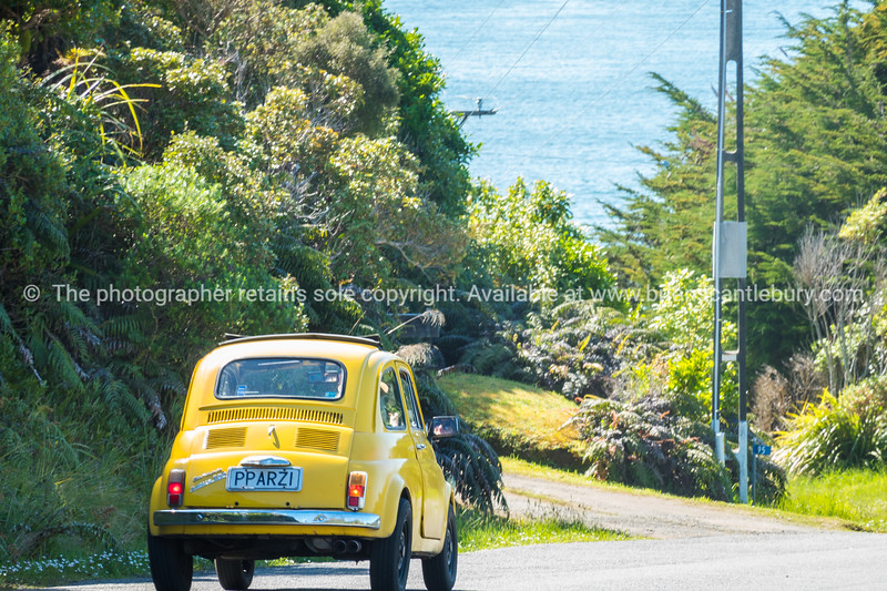 Bright yellow quirky Fiat Bambina on road