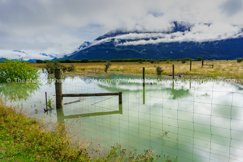 Flooded farmland with fence and water reflected