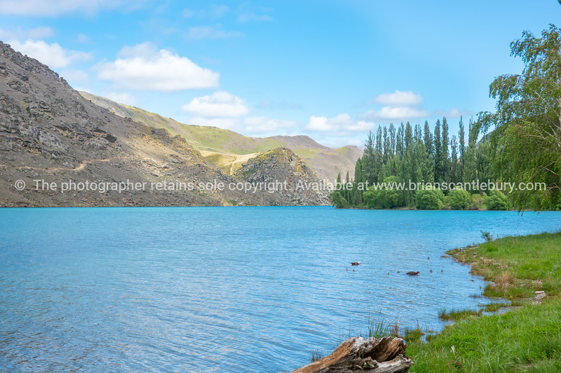 Clutha River with sun on scenic grassy slopes and turquoise river under blue sky