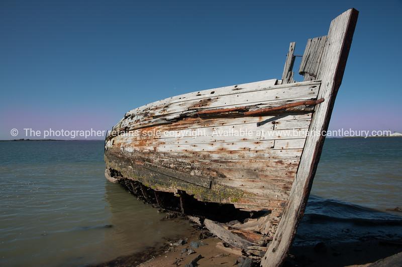 Rotting holed hulk of old wooden fishing boat beached
