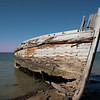 Rotting holed hulk of old wooden fishing boat beached